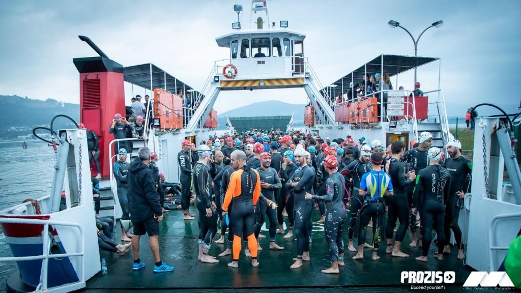 Os triatletas são transportados de ferry e saltam para a água até à linha de partida